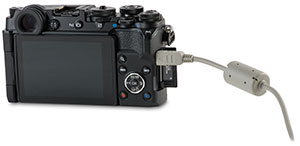 Olympus PEN-F camera with door open and USB cable transfer